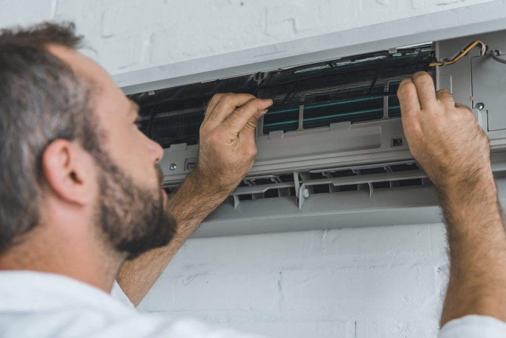 male bearded worker repairing air conditioner